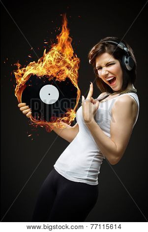 Half-length portrait of teenager with headphones and fiery record in hands on black background