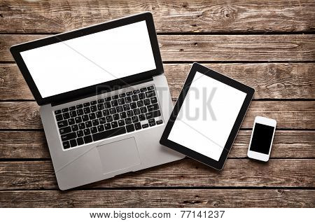 Open laptop with digital tablet and white smartphone. All with isolated screen on old wooden desk.