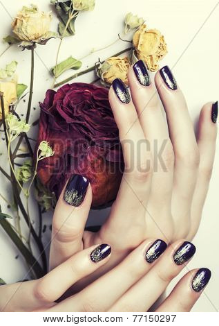 close up picture of manicure nails with dry flower red rose