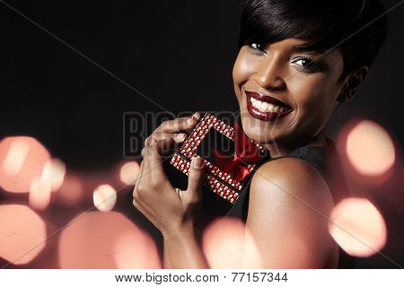 Beauty Woman With A Gift. Bokeh On A Background