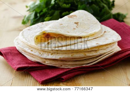 stack of homemade whole wheat flour tortillas on a wooden table