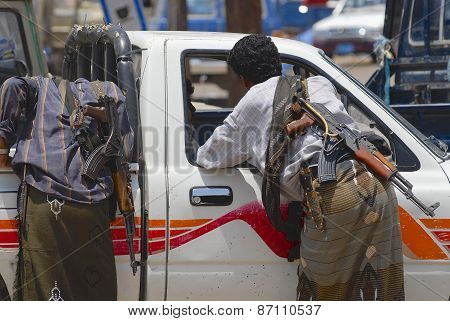Yemeni people with Kalashnikov machine guns talk to a car driver in Aden, Yemen.