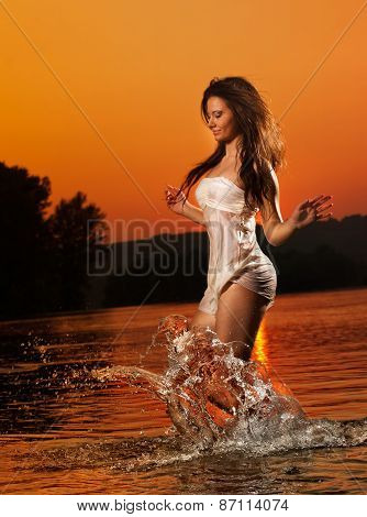 Sexy brunette woman in swimsuit running in river water. Sexy young woman playing with water