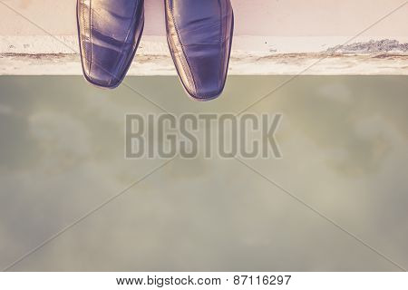 Feet With Black Shoe Standing On Cement Edge