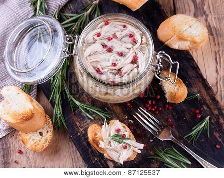 Traditional french dish rillette sort of pate. Chicken pate in glass jar and toast bread on black rustic kitchen board poster