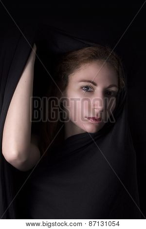 Woman face appear from black background