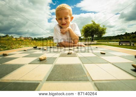 Draughts board game. Little boy clever child kid playing checkers thinking outdoor in the park. Childhood and development poster