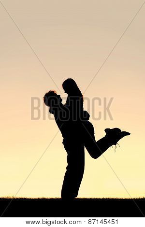 Silhouette Of Happy Young Couple Hugging Outside At Sunset