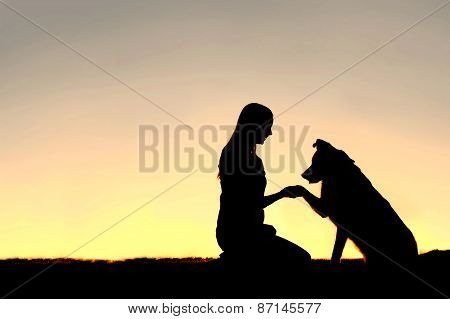 Silhouette Of Young Woman And Pet Dog Shaking Hands At Sunset