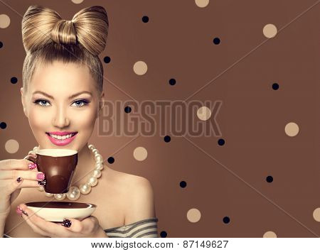 Beauty fashion model girl drinking coffee or tea. Beautiful young woman with cup of hot beverage. Retro styled vintage lady with professional make up, funny bow hair style. Polka dots brown background