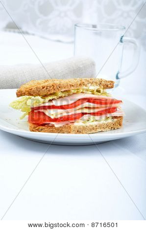 Fresh And Delicious Classic Club Sandwich Over A White Glass Dish With Glass Cup