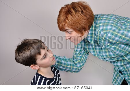 Woman scolding and pulling the ear of the scared young boy poster