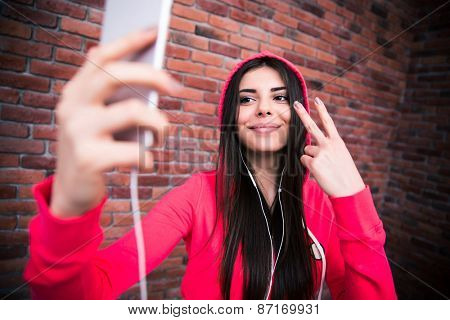 Happy beautiful woman making selfie photo on smartphone. Wearing in sportive cloth. Standing over brick wall poster