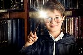 A boy stands with magic wand in the library by the bookshelves with many old books. Fairy tales. Vintage style. poster