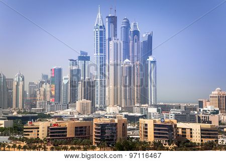 DUBAI, UAE - 2 APRIL 2014: Skyscrapers of Dubai Marina in sunny day, UAE. Dubai Marina is a district in Dubai with artificial canal city who accommodates more than 120,000 people.