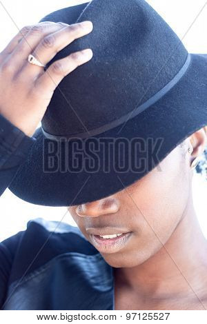Close up Stylish African Woman Holding her Hat on Head with Half-Face Covered Against White Background.