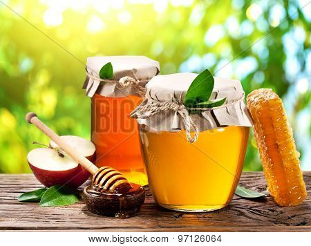 Glass cans full of honey, apples and combs on old wooden table in the garden. poster