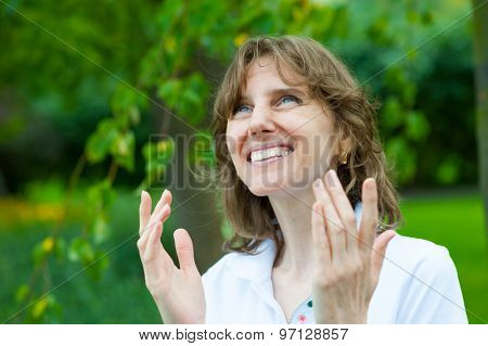 Smiling middle age woman enjoys nature in a park