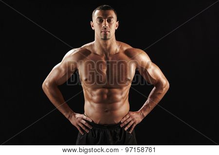 Bare chested male body builder with hands on hips