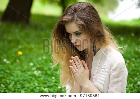 Young beautiful girl praying sitting on the green lawn in the summer park