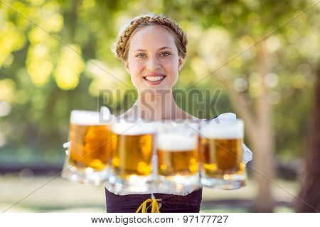 Pretty oktoberfest blonde holding beers on a sunny day