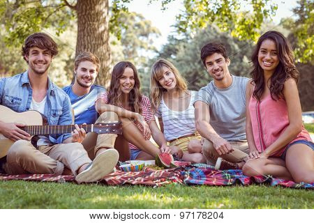 happy friends in a park having a picnic in a sunny day