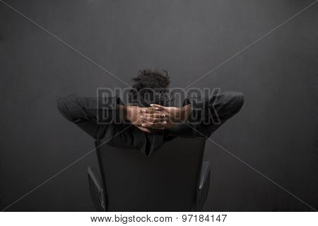 African Woman Sitting On Chair With Arms Behind Head On Blackboard Background