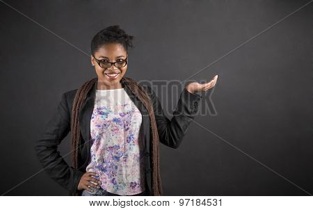African Woman Holding Hand Out On Blackboard Background
