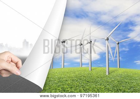 Woman Hand Turning Gray Cityscape Page Revealing Wind Turbines