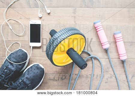 Flat lay of sport equipments and smartphone on wood background. Workout and Healthy lifestyle top view