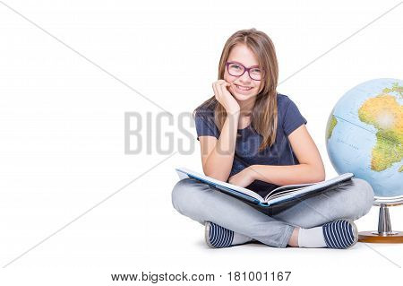 Cute little student girl with globe and book. Girl with glasses and teeth braces. School Education Concept.