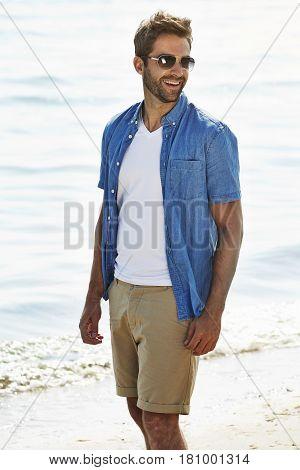 Guy in shorts and shirt at beach smiling