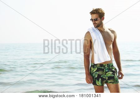 Handsome summer Vacation guy in shorts by sea