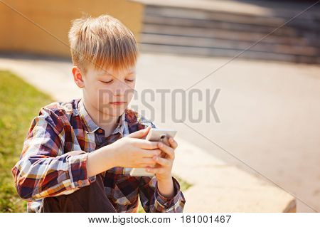 Child playing phone outdoors in sunny day. Boy looking to phone playing games or using application