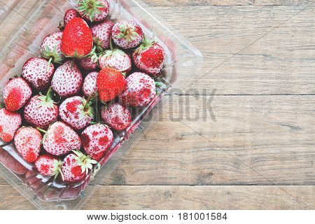 Flat lay of frozen strawberries in box on wooden background Top view