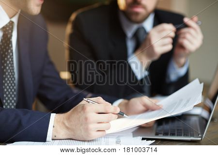Closeup portrait of two unrecognizable  business partners reviewing paperwork and signing contract papers at table during meeting