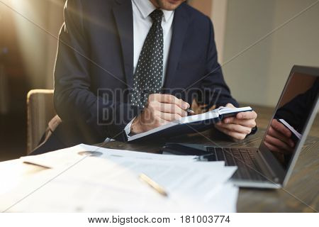Closeup portrait of unrecognizable successful businessman wearing black formal suit  writing in planner while working with documentation and laptop