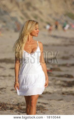 Beautiful Woman In White Dress Walking At The Beach.