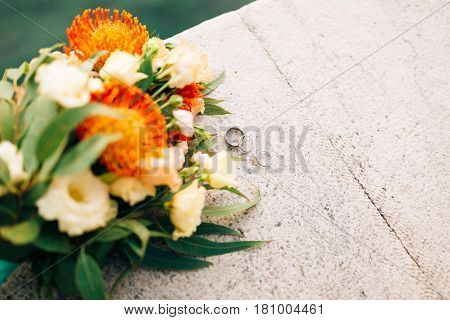 Wedding rings and bunch of Proteus, Verdure Italian , Lisianthus on the stone steps. Wedding jewelry.