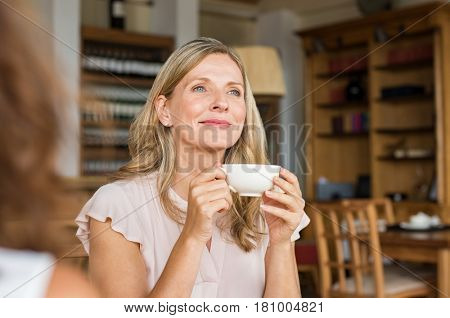Mature woman holding coffee cup and looking away at cafeteria. Thoughtful mature woman thinking while holding coffee cup. Happy and satisfied woman enjoying cappuccino at cafe. poster