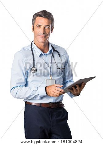 Confident mature medical doctor looking at camera. Senior doctor holding digital tablet isolated on white background. Proud informal doctor using tablet.