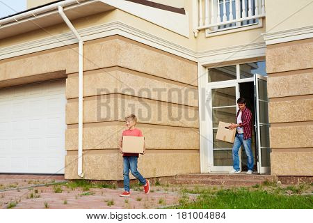 Little boy and his father with boxes leaving their house