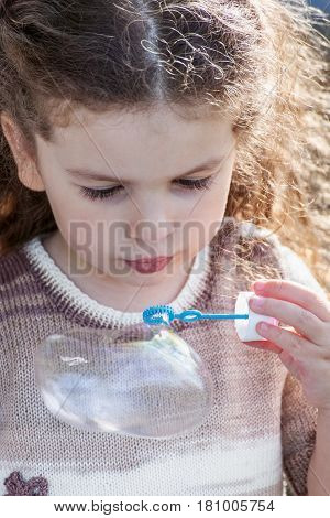 Portrait of little girl blow bubbles outdoors