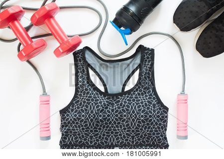 Flat lay of sport equipments with sport bra on white background Overhead view Top view