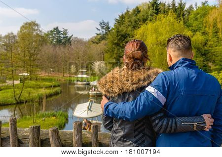 Young man and woman have the arms around eachother while they watch from a wooden bridge to the small slow-moving boats in the water. It's a sunny day in spring.