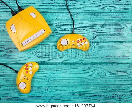 Two yellow joystick and game console on a blue wooden background. Video game console GamePad. Top view. Flat lay