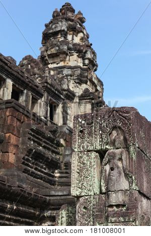 Ancient skilful stone carving in the background of the tower of the temple Baphuon.