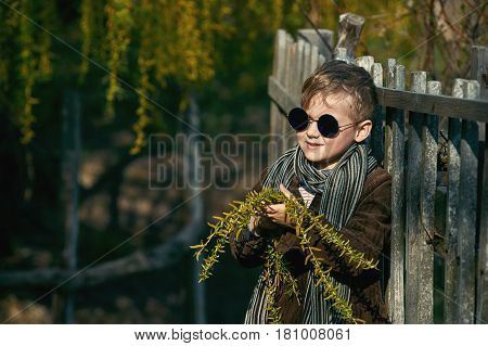 Stylish retro portrait of a boy in the countryside . The boy holds in his hands the flowering branches