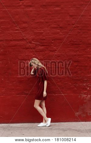 Beautiful woman in red dress against red wall