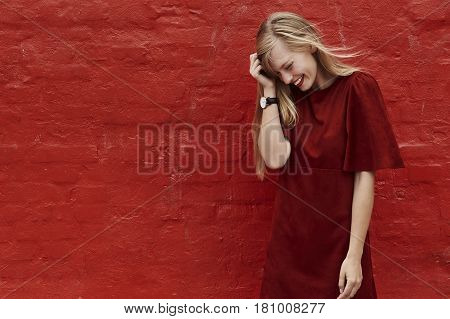 Red dress babe laughing against red wall